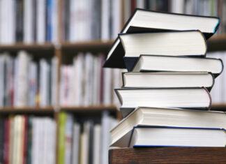 Bücherstapel vor Bücherregal im Hintergrund